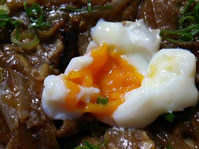 十和田風牛バラ焼重の半熟卵を割る