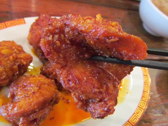 タイガー軒揚げ鶏の四川辛味だれ定食の揚げ鶏を持ち上げる