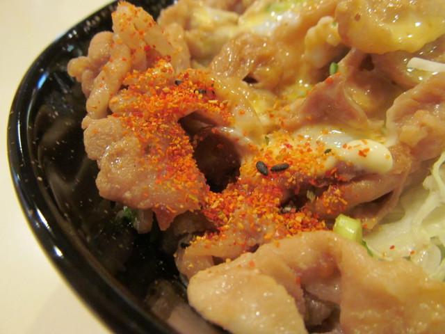 ガスト豚肉スタミナ丼ランチ温玉添えに七味をかける