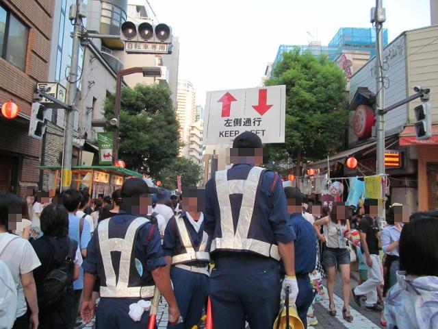 豆源本店前交差点で左側通行を指示する人たち20150822