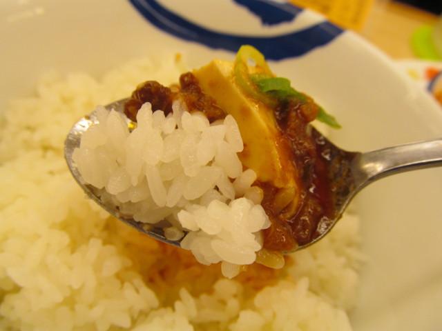 松屋四川風旨辛麻婆豆腐定食の麻婆豆腐とライスを持ち上げ