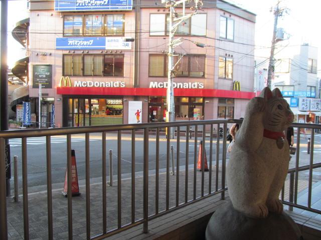 豪徳寺駅前の招き猫の向こうにマクドナルド