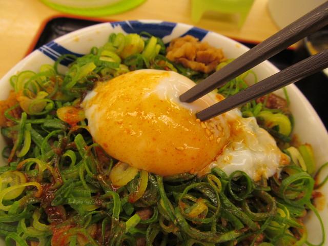 松屋ネギたっぷり旨辛ネギたま牛めしの半熟玉子に箸を入れる