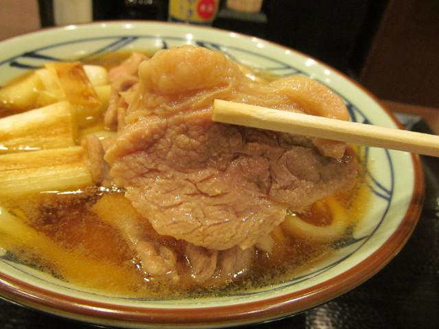 丸亀製麺鴨ねぎうどんの鴨ロースを持ち上げ