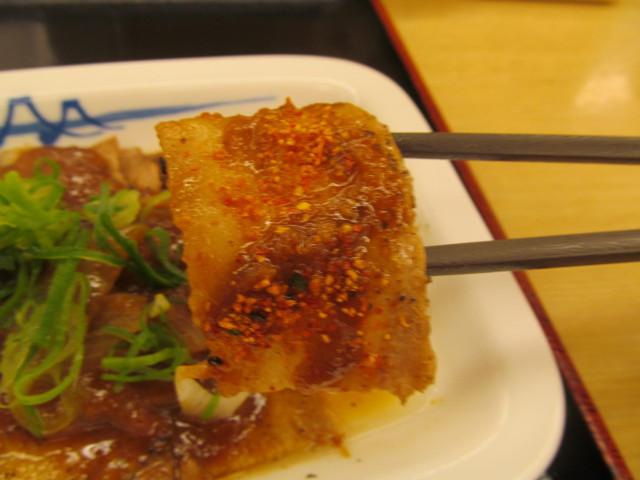 松屋豚バラにんにく味噌定食の七味唐辛子載せ豚バラ肉を持ち上げ