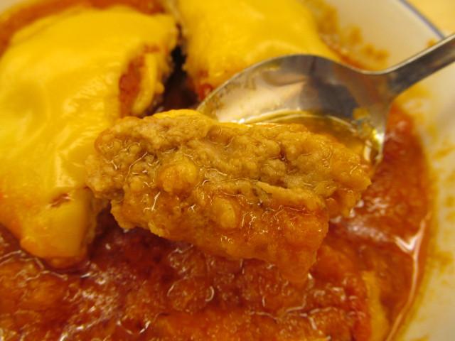 松屋トマトチーズハンバーグ定食のハンバーグを1切れ持ち上げ
